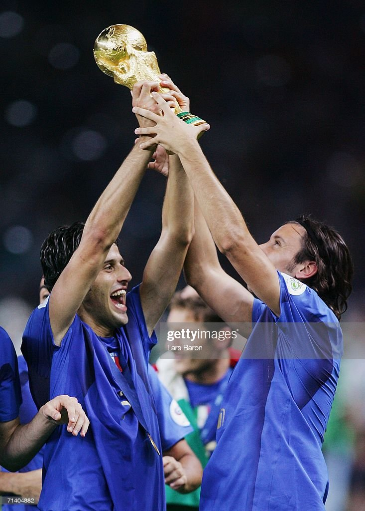 Fabio Grosso (L) of Italy holds the World Cup trophy aloft following his team's victory in a penalty shootout at the end of the FIFA World Cup Germany 2006 Final match between Italy and France at the Olympic Stadium on July 9, 2006 in Berlin, Germany.