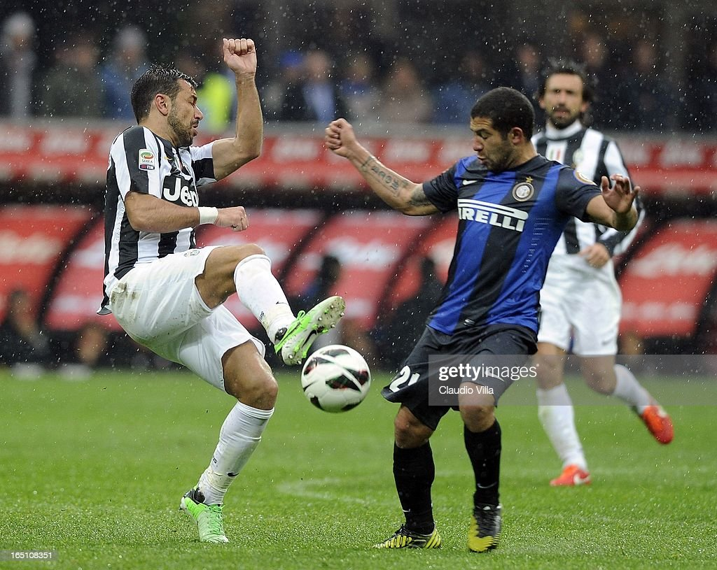 Fabio Quagliarella of Juventus FC (L) and Walter Gargano of FC Inter Milan compete for the ball during the Serie A match between FC Internazionale Milano and Juventus FC at San Siro Stadium on March 30, 2013 in Milan, Italy.