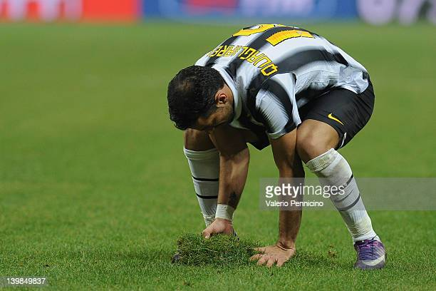 Fabio Quagliarella of Juventus FC attempts to mend the pitch by replacing a piece of turf that has come loose during the Serie A match between AC...