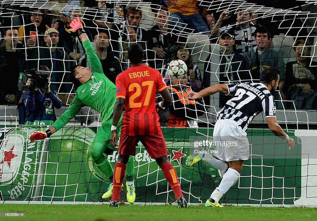 Fabio Quagliarella #27 of Juventus scores his team's second goal past goalkeeper Fernando Muslera, watched by Emmanuel Eboue of Galatasaray AS during UEFA Champions League Group B match between Juventus and Galatasaray AS at Juventus Arena on October 2, 2013 in Turin, Italy.