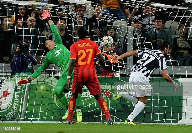 Fabio Quagliarella of Juventus scores his team's second goal past goalkeeper Fernando Muslera watched by Emmanuel Eboue of Galatasaray AS during UEFA...
