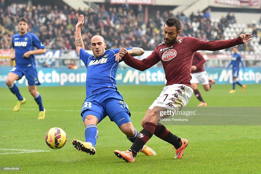 Fabio Quagliarella (R) of Torino FC is challenged by Paolo Cannavaro of US Sassuolo Calcio during the Serie A match between Torino FC v US Sassuolo Calcio at Stadio Olimpico di Torino on November 23, 2014 in Turin, Italy.