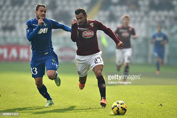 Fabio Quagliarella of Torino FC is tackled by Matteo Brighi of US Sassuolo Calcio during the Serie A match between Torino FC v US Sassuolo Calcio at...