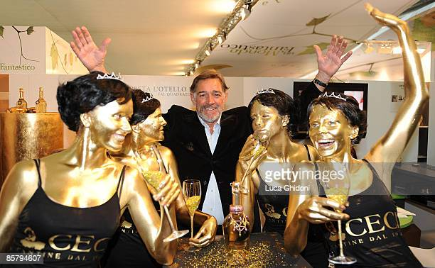 Fabio Testi poses with painted models at the Vinitaly on April 3 2009 in Verona Italy Vinitaly the international wine and spirit exhibition runs...