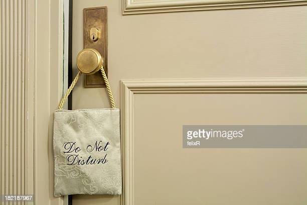 A fabric 'do not disturb' sign hanging on a cream door