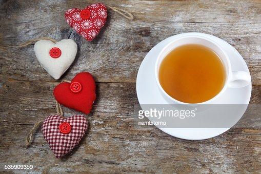Tela de corazones y taza de té sobre fondo de madera : Foto de stock