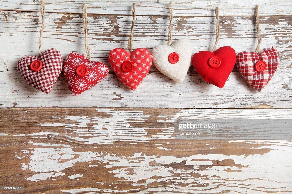 Material mit Herzen auf einem hölzernen Hintergrund : Stock-Foto