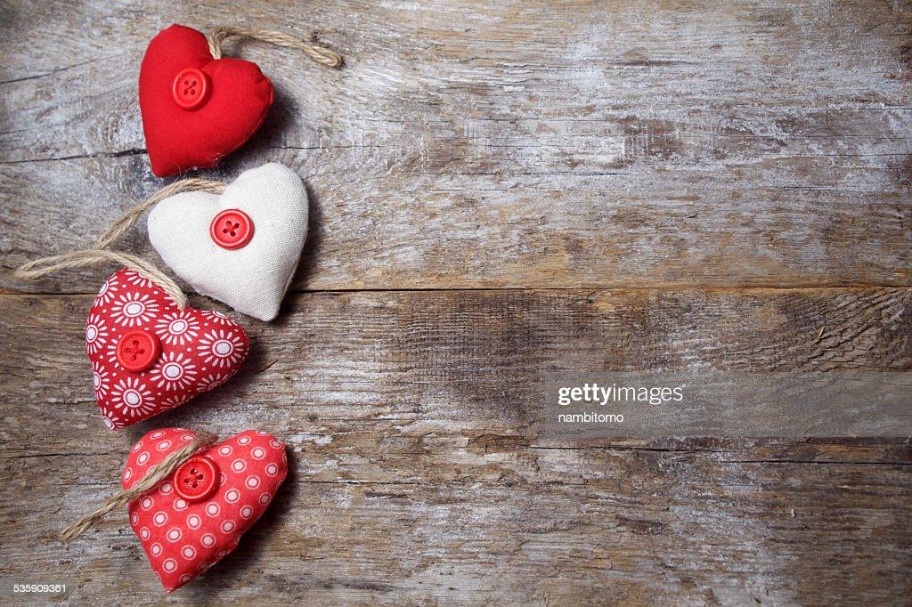 Tecido de corações em um fundo de madeira : Foto de stock