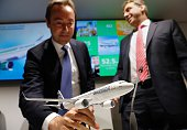 Fabrice Bregier President and CEO of Airbus picks up a model Airbus A320 as he and Karsten Balke CEO of Germania address a press conference at the...