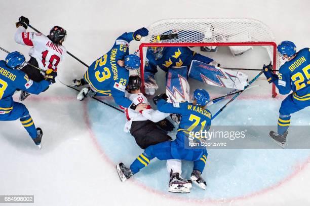 Fabrice Herzog vies with William Karlsson #23 Oliver EkmanLarsson and Goalie Henrik Lundqvist during the Ice Hockey World Championship Quarterfinal...