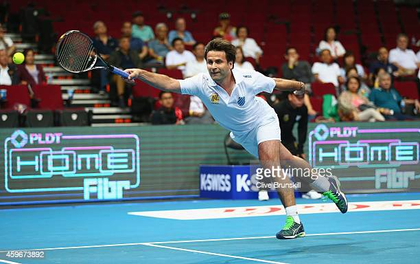 Fabrice Santoro of the Indian Aces stretches to play a forehand against Patrick Rafter of the Singapore Slammers during the CocaCola International...