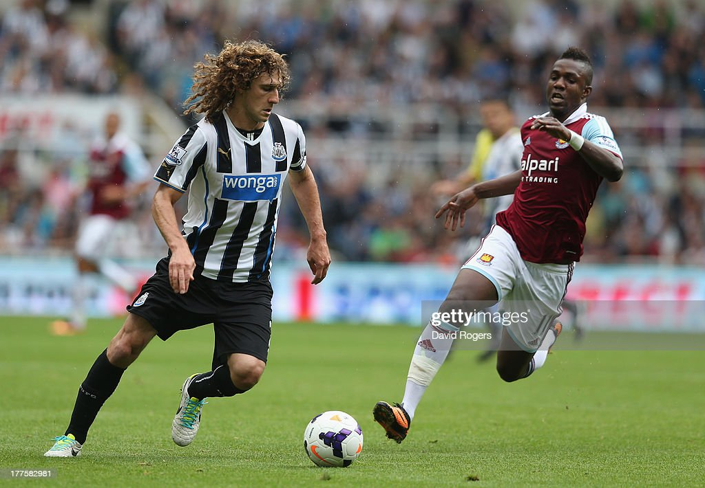 Fabricio Coloccini of Newcastle United is challenged by Modibo Maiga during the Barclays Premier League match between Newcastle United and West Ham United at St James' Park on August 24, 2013 in Newcastle upon Tyne, England.