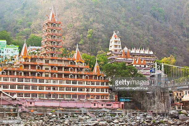 Facade of a multistoried temple at the riverside Trayambakeswar Temple Lakshman Jhula River Ganges Rishikesh Dehradun District Uttarakhand India
