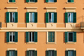 Part of the facade of an orange italian building with windows with green shutters
