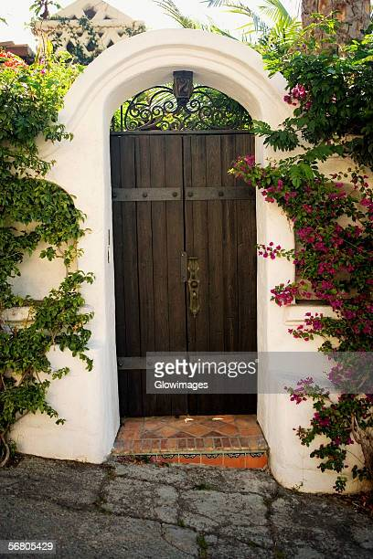 Facade of wooden doors in a stucco arch, Los Angeles, California, USA