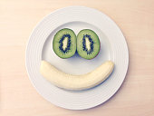 Face Made From Banana And Kiwi On Plate