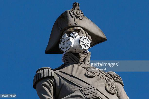 A face mask is placed on the statue of Nelson's Column by Greenpeace protesters on April 18 2016 in London England The demonstration was to highlight...