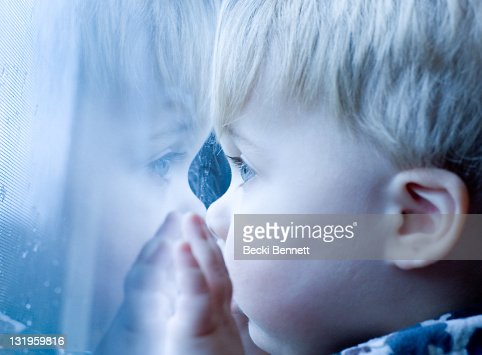 Face of boy looking out window with raindrops : Stock Photo