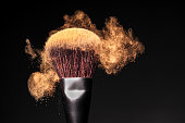 Face powder in motion on a make-up brush - Makeup Concept Background