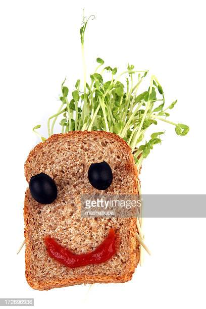 Face sandwich with sprout hair, olive eyes and ketchup smile