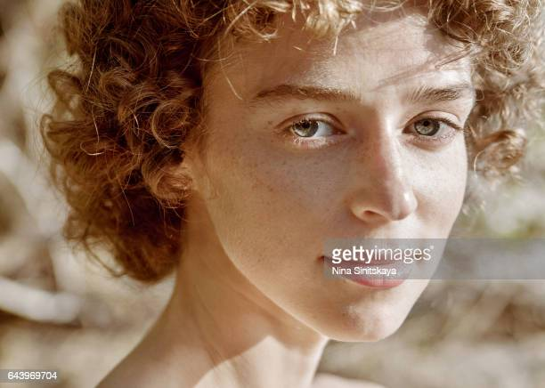 Face shot of curly woman with freckles on the beach