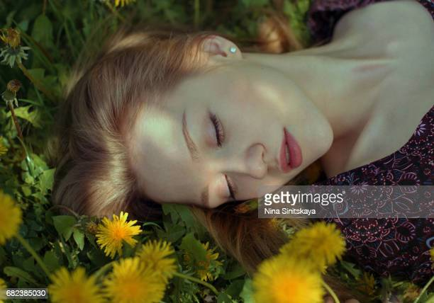 Face shot of woman lays in grass with dandelion flowers