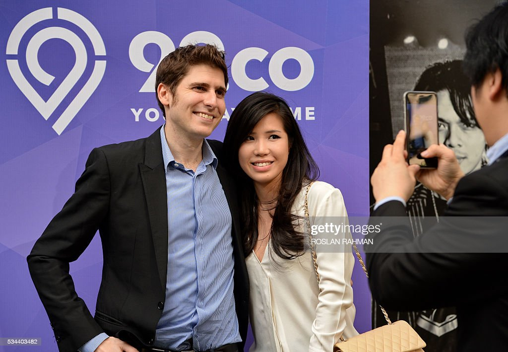 Facebook co-founder Eduardo Saverin (L) and his wife Elaine Andriejanssen (R) attend the 99.co second Anniversary and 99PRO Launch in Singapore on May 26, 2016. / AFP / ROSLAN