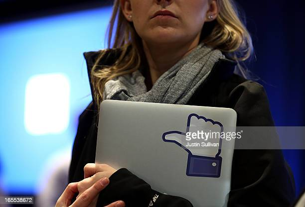 Facebook employee holds a laptop with a 'like' sticker on it during an event at Facebook headquarters during an event at Facebook headquarters on...