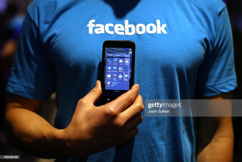 A Facebook employee holds a phone that is running the new 'Home' program during an event at Facebook headquarters during an event at Facebook headquarters on April 4, 2013 in Menlo Park, California. Facebook CEO Mark Zuckerberg announced a new product for Android called Facebook Home as well as the new HTC First phone that will feature the new software.