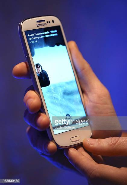 Facebook employee holds a phone that is running the new 'Home' program during an event at Facebook headquarters during an event at Facebook...