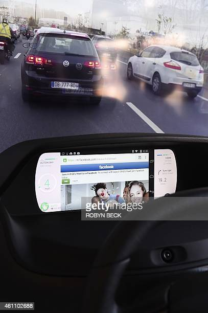 Facebook from a wirelessly connected smartphone is seen on the mockup display of the Mobi/us autonomous dashboard by Valeo a concept for interacting...