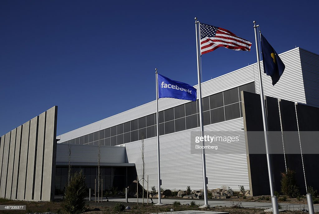 A Facebook Inc. flag flies next to a U.S. flag outside the company's Prineville Data Center in Prineville, Oregon, U.S., on Monday, April 28, 2014. The Facebook Prineville Data Center features leading energy-efficient technology, including features such as rainwater reclamation, a solar energy installation for providing electricity to the office areas and reuse of heat created by the servers to heat office space. Photographer: Meg Roussos/Bloomberg via Getty Images
