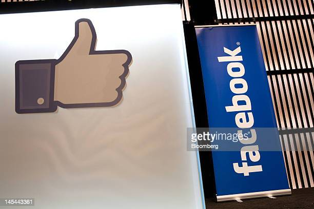 A Facebook Inc social media logo and a 'like' symbol stand on display during a news conference at the Armani Hotel to announce the opening of a...