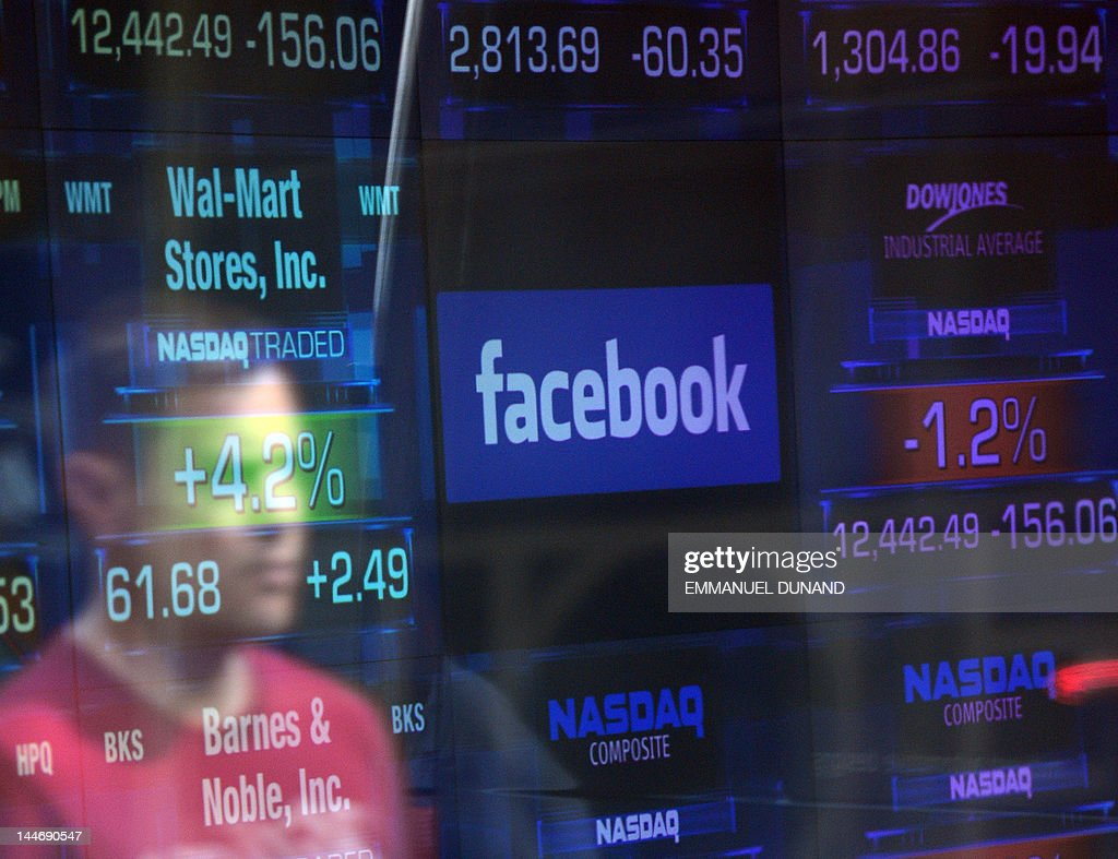 A Facebook logo is seen through the windows of the NASDAQ stock exchange as people walk by on Times Square in New York, May 17, 2012. Facebook is set to go public on May 18, 2012 and is likely to have an estimated market valuation of over 100 billion USD when its shares begin trading on the NASDAQ. AFP PHOTO/Emmanuel Dunand