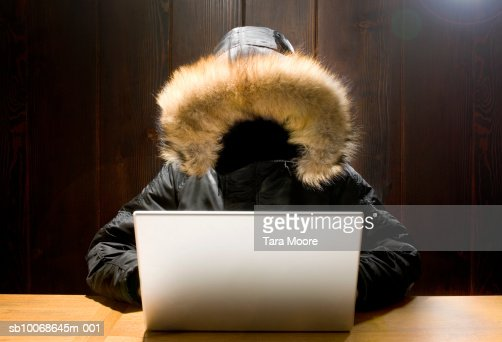 Faceless person using laptop at desk (Digital Composite)
