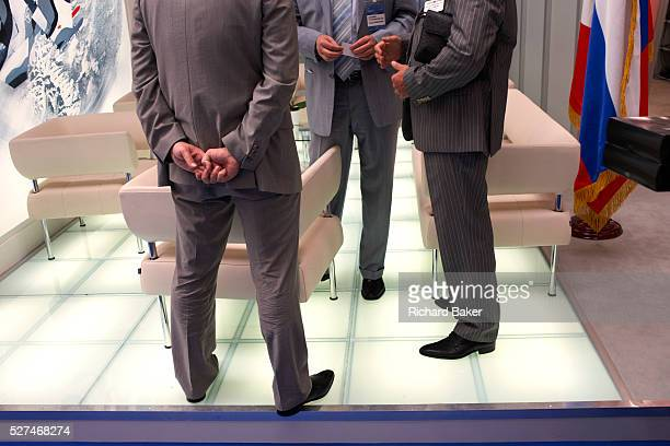 Faceless Russian delegates are in deep discussion in a hall at the Paris Air Show Le Bourget France With the flag of the Russian Federation...