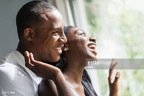 Faces of young black couple looking out window, laughing