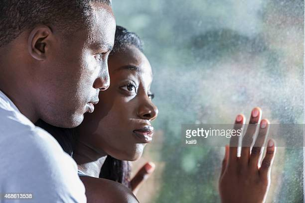 Faces of young black couple looking out window
