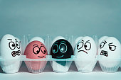 Faces on eggs in the form of facial expressions, reflecting emotions. The concept of racism, misunderstanding, a barrier in relations, denial of society.