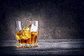 Faceted glass of whiskey with ice on dark background