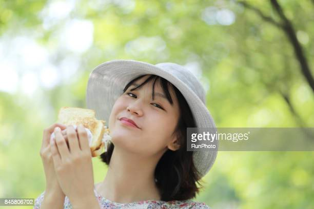 Facial expression of a woman who ate bread while watching a camera