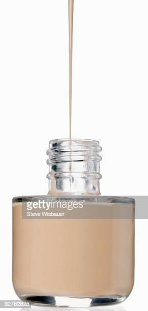 Facial foundation pouring into isolated bottle