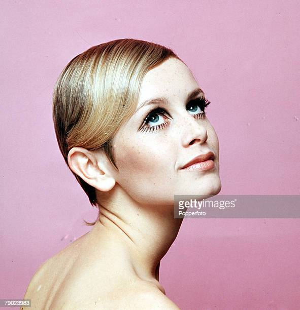 1967 A facial portrait of model Twiggy wearing black eyelash makeup whilst looking up smiling