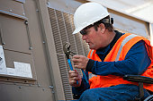 Facilities engineer in a wheelchair opening inspection plate of commercial air conditioning system