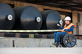 Facilities engineer in a wheelchair pulling caution tape in front of chemical storage tanks