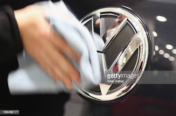 A facilities worker wipes clean the VW logo on a car at a Volkswagen Group showroom on January 14 2013 in Berlin Germany Volkswagen Group which...