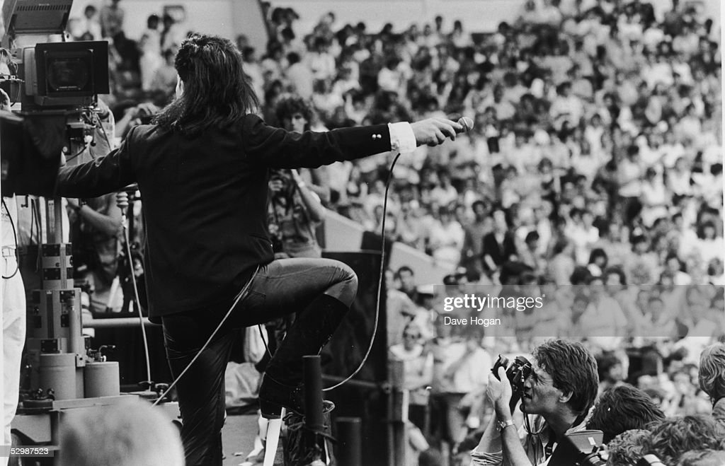 Facing the television cameras, Irish singer Bono holds out his microphone to the crowd during U2's performance at the Live Aid charity concert, Wembley Stadium, London, 13th July 1985.