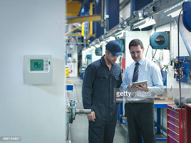 Factory and office worker discussing energy saving in factory