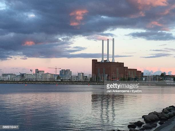 Factory By Lake Against Sky During Sunset In City