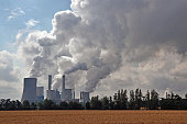 Factory chimneys emitting air pollutions. View through the field on clouds of smoke and factory.